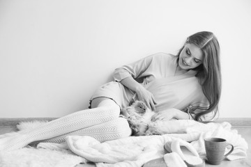Beautiful young woman with cute funny cat resting at home