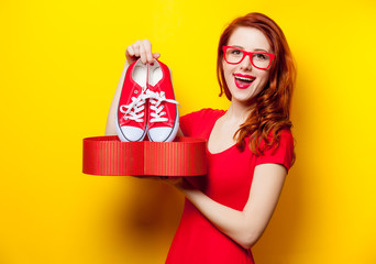 photo of beautiful young woman holding gumshoes under heart shaped box on the wonderful yellow studio background