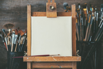 Artistic equipment in a artist studio: empty artist canvas on wooden easel and paint brushes Retro toned photo.
