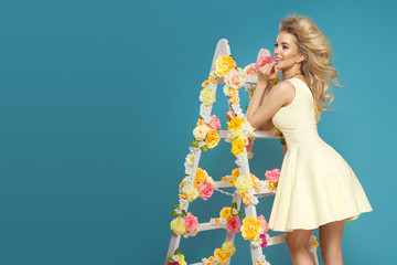 Delicate blonde woman with floral white lAdder