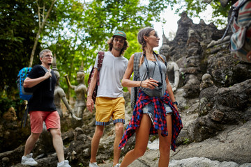 four tourists walking through ancient jungle ruins in thailand