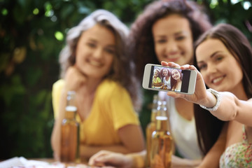 Woman showing photo of herself with friends on smart phone