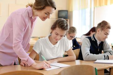 Teacher explaining exercise to pupil in classroom