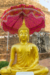 The Golden buddha with umbrella tiered on the ancient pagoda background .