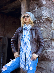 A blonde caucasian woman in leather jacket and torn jeans near the brick ruin wall.