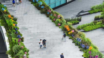 top aerial view people are walking on the bridge pedestrian hardscape and landscape green area garden walkway in the business city area.
