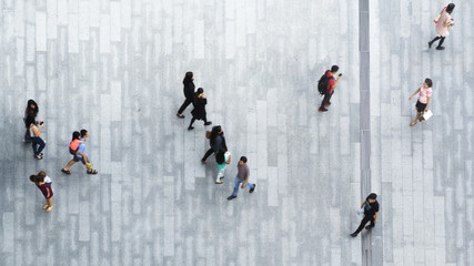 people walk on across the pedestrian concrete landscape in the city street (Aerial top view)