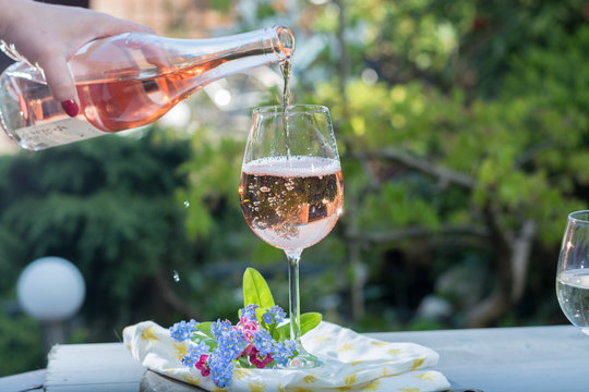 Waiter pouring a glas of cold rose wine, outdoor terrase, sunny day