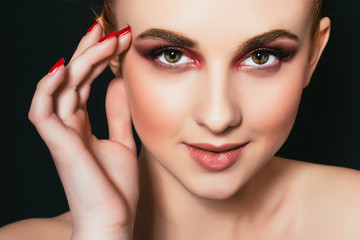 Beautiful girl with pink make-up and smooth skin close-up on a dark background