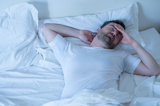 Upset man trying to sleep in his bed at night
