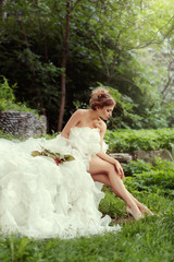 Beautiful woman bride looking at her long legs in nature in the forest sitting on the grass.