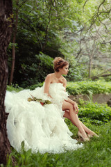 Portrait of a beautiful bride woman sits in a profile and looks into the distance in nature.