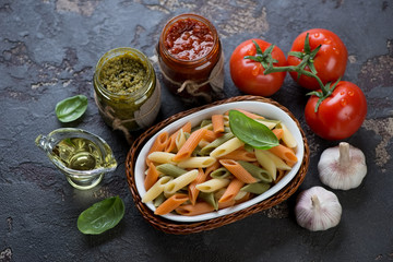 Penne of italian flag colors with red pesto and basil pesto and other cooking ingredients, horizontal shot