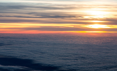 Sunset in sky view from plane flying over sea of clouds