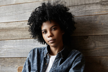 Indoor shot of stylish young Afro American female with curly hair wearing trendy denim clothing looking at camera with neutral calm expression, sitting on chair at coffee shop, waiting for friends