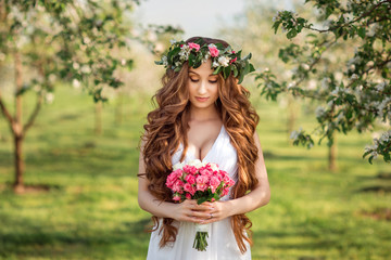 Beautiful bride with long hair and a wreath of flowers on her head holding a bouquet.