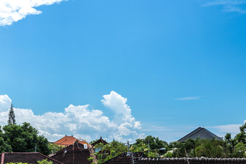 Blue sky with clouds, balinese landscape, tropical Bali island, Indonesia. Balinese houses.