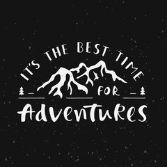 Phrase It's the best time for adventures on dark background. Handwritten lettering for cards, posters and t-shirts. Outdoor vector illustration with quote and mountains silhouette.