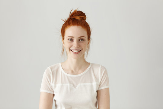 Cheerful gorgeous young woman wearing her ginger hair in knot smiling happily while receiving some positive news. Pretty girl dressed in white blouse looking at camera with excited joyful smile