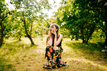 Happy and attractive beautiful artistic young model girl in colorful dress with long hair in summer lilac garden with bushes and flowers posing for camera. Spring concept.