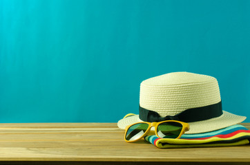 Sunglasses and hat resting on the wooden floor with blue background. accessories for summer