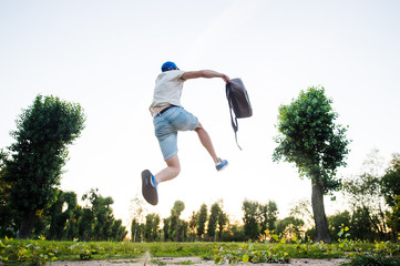 Young man summer dressed going to vacation after finishing his job and jumping to the sky with a bag at his hand in  sunny day with the trees at horizon. Vacation and freedom concept