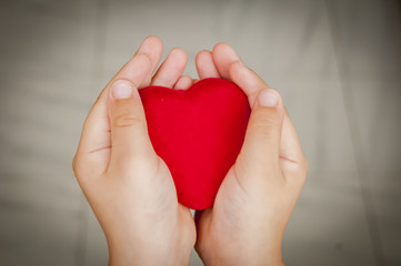 Child holds a big red heart in his hands. Sincerity, sincere love stock image.