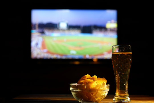 Glass of cold beer and chips, baseball match in background. Evening watching baseball
