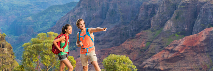 Hiking couple looking at view in mountain nature during hike in Waimea Canyon State Park, Kauai, Hawaii, USA. Caucasian man pointing at mountains for Asian woman, backpackers. Banner panorama.