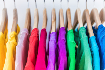 Fashion clothes on clothing rack - bright colorful closet. Closeup of rainbow color choice of trendy female wear on hangers in store closet or spring cleaning concept. Summer home wardrobe. Wall mural