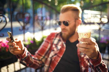 A cup of coffee.  Bearded man with paper cup of morning coffee walking