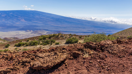 Red lava rocks on Mauna Kea, Mauna Loa in the background, colored blue from the atmosphere.