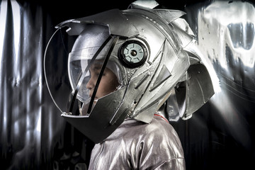Boy playing to be an astronaut with a space helmet and silver suit on metallic background
