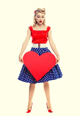 smiling woman holding heart symbol, dressed in pin-up style