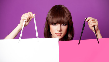 photo of beautiful young woman with colorful shopping bags on the wonderful purple background