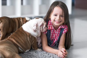 Cute beautiful girl lying on the floor with the puppies English bulldog
