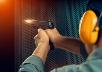 man firing pistol at target indoor shooting range