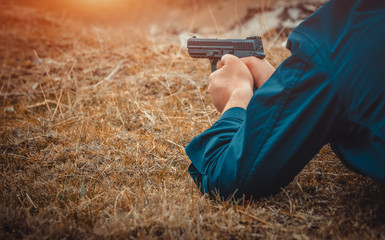 man with pistol lying on ground and waiting for attack. hitman waiting in ambush.