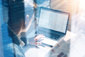 Closeup view of banking finance analyst in eyeglasses working at sunny office on laptop while sitting at wooden table.Businessman analyze stock report on notebook screen.Double exposure concept.