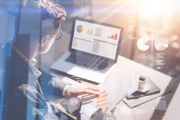 Young businessman analyze stock report on notebook screen.Concept of digital screen,virtual connection icon,diagram,graph interfaces on background.Double exposure.