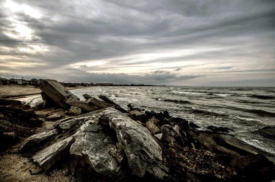 Sunset at the sea shore of a beach with rocks and stormy waves, beautiful seascape at Caspian sea Absheron, Azerbaijan Novkhani