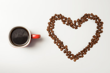 cup of hot coffee and heart made of coffee beans on the white table