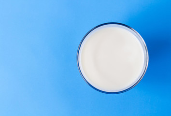 Closeup top view milk glass on blue background, healthy food concept