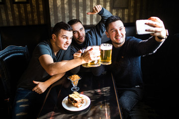 happy male friends taking selfie and drinking beer at bar or pub on party