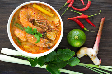 Tom yum kung in white bowl and ingredients on wooden table
