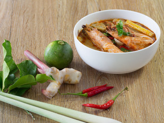 Tom yum kung in white bowl and ingredients on wooden table .