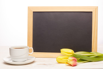 Blank board, flowers and cup of coffee.