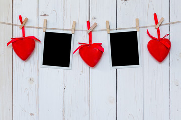 Photo frame blank and red heart hanging on white wood background with space
