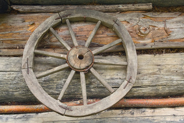 Wooden wheel from an ancient cart hanging on the wall of the hut