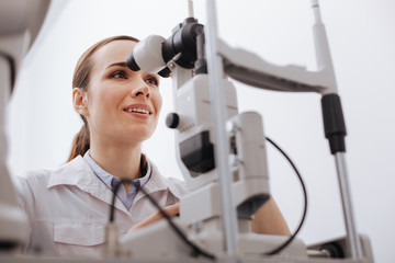 Cheerful experienced optician using medical equipment